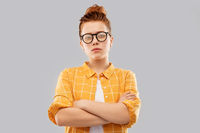 redhead student girl in glasses with crossed arms