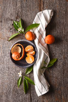 Closeup of a peeled orange on a plate with towel and leaves on a rustic wood table