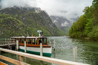 Scenic view on Konigssee Lake with wooden pier with moored touristic ship