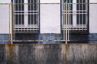 Korrodierender Gitterzaun vor Fassade