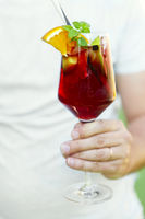Glass of iced sangria with strawberry, orange, apple and lemon in the hand of the man
