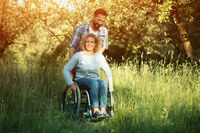 Smiling woman in wheelchair with husband in the park on sunny day