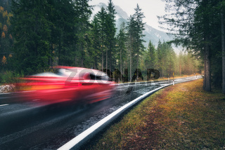Blurred red car in motion on the road in autumn forest in rain