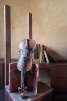 Still life of broken old broken violin and vintage grunge books