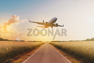airplane flying above  empty road in rural landscape - travel concept