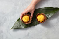 A girl's hand holds a coconut shell with a mango sorbet on a green leaf on a gray concrete background. Top view