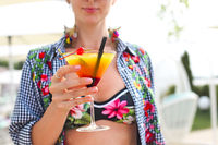 Exotic cocktail glass in womans hand