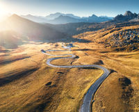 Winding road in mountain valley at sunset in autumn. Aerial view