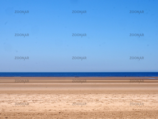 a long sandy beach with blue summer sky and blue sea with a group distant unidentifiable people near the water