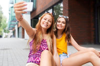 teen girls taking selfie by smartphone in city