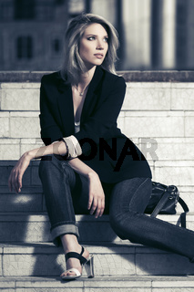 Young fashion business woman sitting on steps