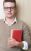 young male college student reading in the library