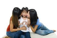 Asian family kissing little girl