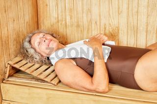 Senior Frau schläft entspannt in der Sauna