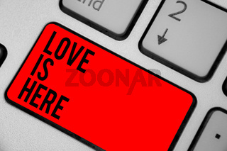 Conceptual hand writing showing Love Is Here. Business photo text Romantic feeling Lovely emotion Positive Expression Care Joy Keyboard red key create computer computing reflection document.