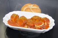 Schale mit Currywurst und Brötchen