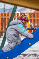 Boy climbing up the slide in winter