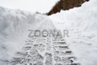 Image of car tracks in white snow