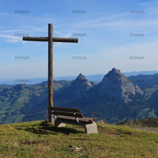Summit cross and bench on the summit of Mount Fronalpstock, Switzerland.
