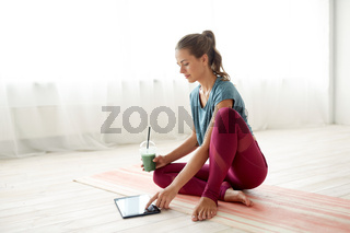 woman with tablet pc and drink at yoga studio