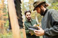 Revierförster kontrollieren Borkenkäferfalle im Wald