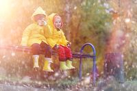 A child in a raincoat for a walk outside in autumn