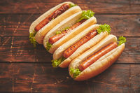 Tasty american hot dogs assorted in row. Placed on wooden table