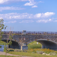 Stone arched bridge overlooking lake and sky