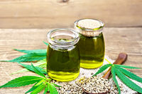 Oil hemp in two jars and spoon on old board