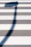 Laternenschatten auf dem Fußgängerweg
