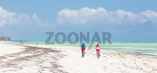 Active sporty tourist couple cycling down picture perfect white sand tropical beach of Paje, Zanzibar, Tanzania.