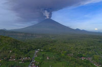 Ashes rising from the volcano. The village at the foot of the volcano in the tropical jungle