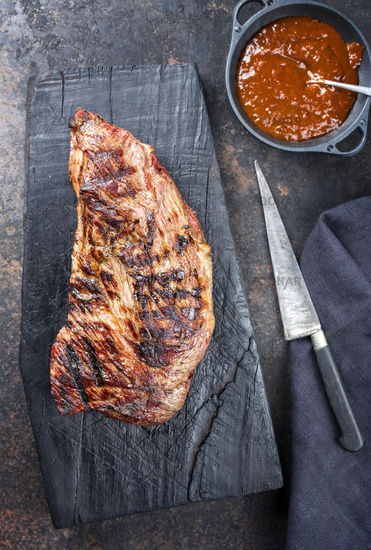 Barbecue dry aged wagyu tri trip steak with BBQ sauce as dip as top view on a carbonized wooden board