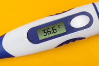 Electronic medical thermometer (36.6 degrees) on yellow background