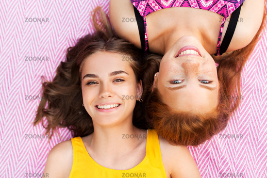 smiling teenage girls lying on picnic blanket