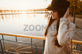 young girl stands on the city embankment by the lake