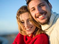 couple on a beach at autumn sunny day