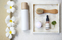 Face cream, serum, lotion, moisturizer and face oil among white frangipani in the bath