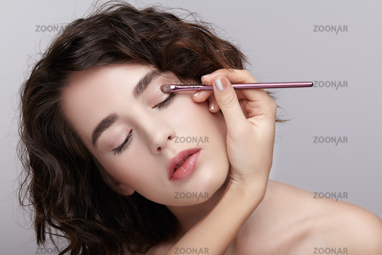 Make-up artist apply beauty makeup on the eyelids of a beautiful girl. Visagist with makeup brush in hand