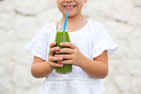 Little girl is drinking green fresh juice using straw outdoors