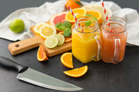 mason jar glasses with juice and fruits on table