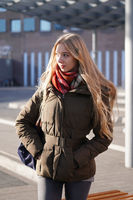 candid street style image of young woman waiting at bus station