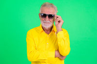 Handsome senior bearded businessman wearing and holding sunglasses
