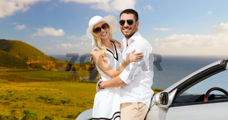 happy couple hugging near convertible car