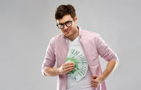 happy young man in glasses with fan of euro money