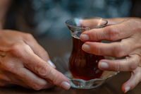 Hands of the elderly woman who holds a glass with tea