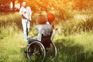 Woman in wheelchair plays with ball with her family outdoors