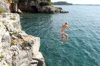 Mädchen springt ins Meer
