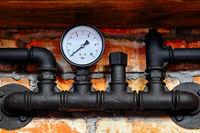 Old black pipeline and pressure gauge