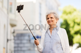 happy senior woman taking selfie on city street